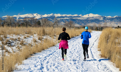 Fototapeta Women running along a snowy trail in Boulder, Colorado with the Continental Divide kin the background