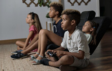 Four Pretty Multi National Kids Play To Play Station Seated Together At Home. Alpha Generation Offspring Addicted With Virtual Games Problem Concept