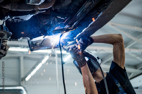 Foto Car mechanic with protective mask welding car. Service station