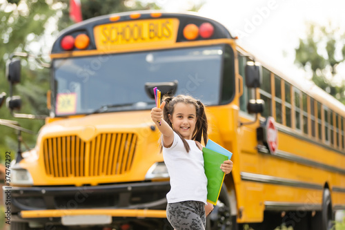 Fotografiet Cute girl with a backpack standing near bus going to school posing to camera pen