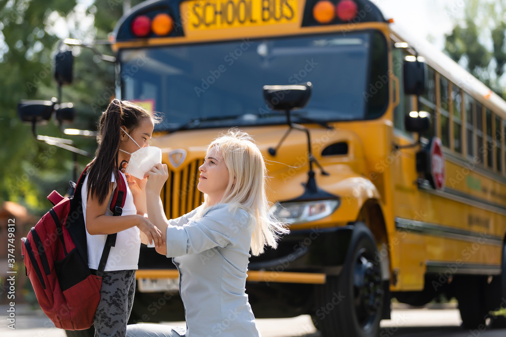 Fototapeta Caucasian woman puts a protective mask on her daughter outdoors. Caring mother helps to wear a mask schoolgirl near the school bus. Quarantine during coronavirus.