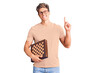 Young handsome man holding chess surprised with an idea or question pointing finger with happy face, number one