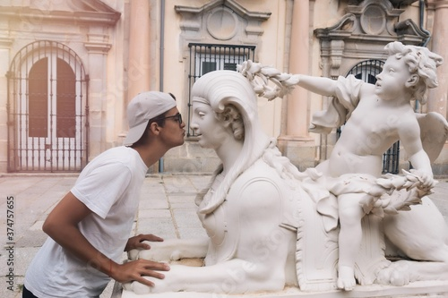Stampa su Tela young teenager in love with a statue he tries to kiss on the mouth