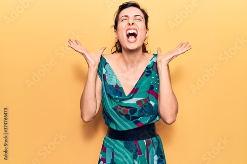 Young beautiful hispanic woman wearing casual dress celebrating mad and crazy for success with arms raised and closed eyes screaming excited Tapéta, Fotótapéta