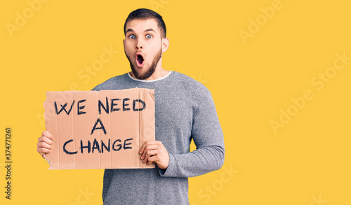 Fotografía Young handsome man holding we need a change banner scared and amazed with open m