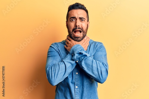 Young hispanic man wearing casual clothes shouting and suffocate because painful strangle Canvas Print