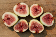 Ripe, Succulent Figs Sliced In Half On A Wooden Cutting Board