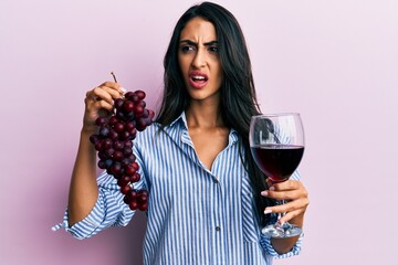 Beautiful hispanic woman holding branch of fresh grapes and red wine angry and mad screaming frustrated and furious, shouting with anger. rage and aggressive concept.