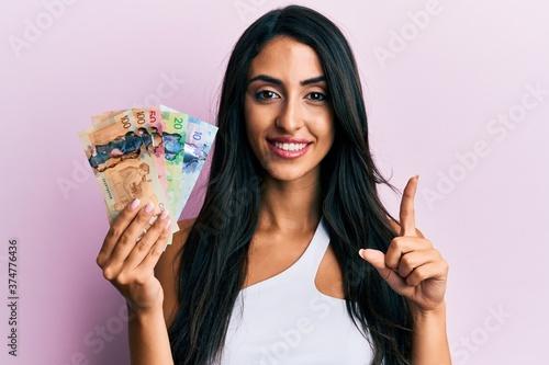 Fotografia Beautiful hispanic woman holding canadian dollars smiling with an idea or questi
