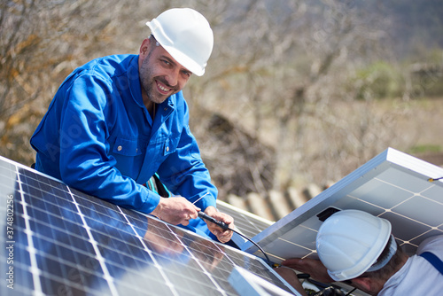 Fotografia Male workers installing stand-alone solar photovoltaic panel system
