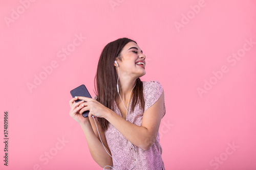 Fényképezés Smiling brown-haired girl enjoying favorite song and dancing in pink top