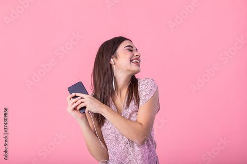 Smiling brown-haired girl enjoying favorite song and dancing in pink top Fototapet
