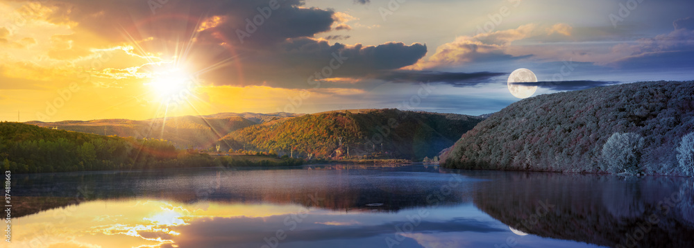 day and night time change concept above mountain lake among the forest. trees in colorful foliage. beautiful panorama in autumn. clouds and sky with sun and moon reflecting in the water