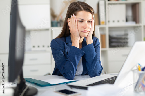 Fotografia Tired young businesswoman working with documents in office