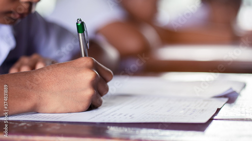 Fototapeta Hand of students writing and taking exam with stress in classroom