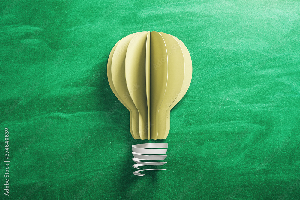 Yellow light bulb made from paper on blackboard background.