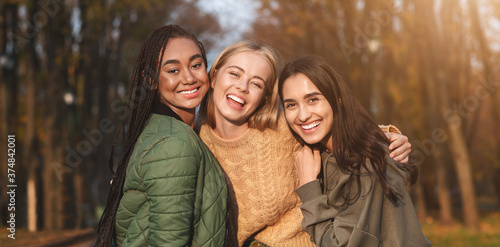 Cuadros en Lienzo Portrait of three young girlfriends spending time in park