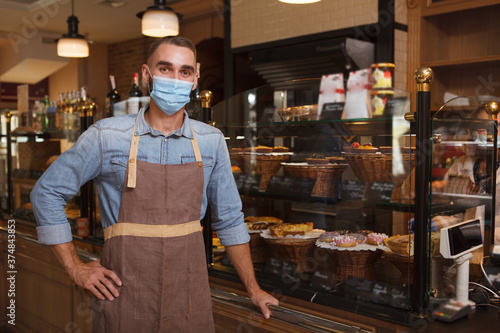 Fotomural Male baker wearing medical face mask working at his bakery store during coronavi