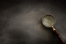 Vintage Magnifying Glass With Wooden Handle Over Chalkboard Background. Top View, Flat Lay