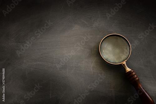 Obraz na plátně vintage magnifying glass with wooden handle over chalkboard background