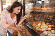 Attractive young woman shopping for pastry at local bakery store, copy space