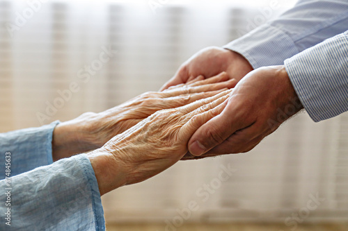 Fototapeta Mature female in elderly care facility gets help from hospital personnel nurse