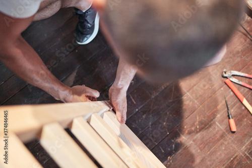 Carpenter hobbyist assembling wooden boards at home / garage. Canvas