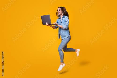 Obraz Full length body size profile side view of nice smart clever slim fit cheerful girl jumping walking using laptop watch video lesson tutorial isolated bright vivid shine vibrant yellow color background - fototapety do salonu