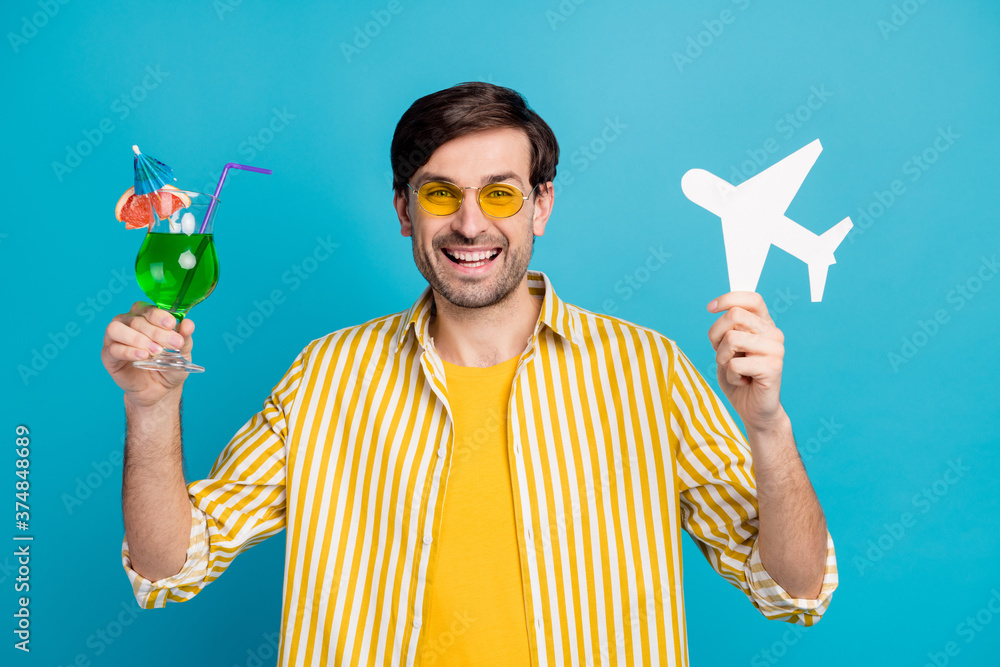 Fototapeta Photo of positive man traveler enjoy travel exotic trip hold alcohol beverage cocktail paper card plane wear yellow white striped shirt isolated over blue color background