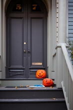 Halloween Pumpkins Sit On The Doorstep, Are They Welcoming Or Warning Of Scary Spooky Surprises For The Trick Or Treaters