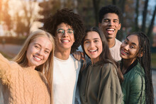 Positive Multiracial Teen Friends Taking Selfie While Walking In Park