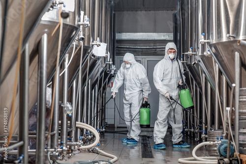 Worker in hazmat suit making disinfection inside beer plant