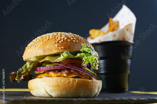 Photo Juicy beef burger with cheese, bacon, tomato, lettuce, dressings, avocado, red onion and accompanied by french fries
