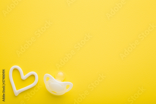 White silicone baby soother and heart shape on bright yellow table background Tapéta, Fotótapéta