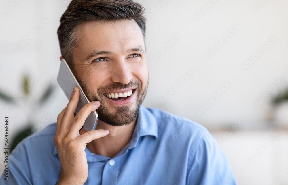 Fototapeta Closeup portrait of smiling handsome young businessman talking on mobile phone indoors
