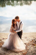 canvas print picture - A beautiful wedding couple on the riverbank at sunset. A woman in a gray dress with flowers, a man in a suit and suspenders hug each other, love. Lovers on a walk