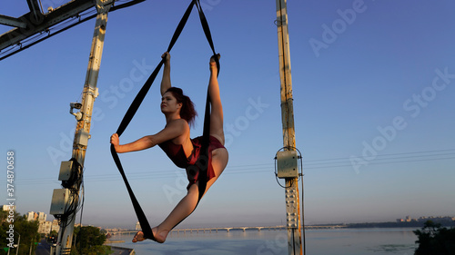 Fotografie, Tablou Circus performer on aerial straps performs an aerial act at dawn
