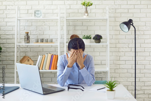 Fotografía Exhausted young woman working overtime at office