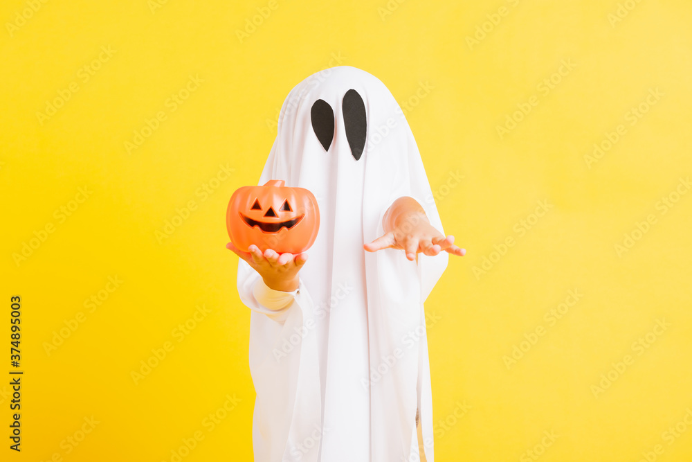 Fototapeta Funny Halloween Kid Concept, little cute child with white dressed costume halloween ghost scary he holding orange pumpkin ghost on hand, studio shot yellow on white background