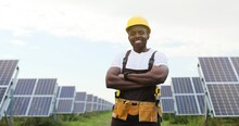 Portrait Of African American Engineer At Solar Power Station With Solar Panel.