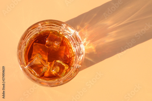 Obraz na plátne Glass of cold whiskey on beige background with sunny shadow.