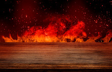 Side View Of Empty Wooden Table Top With Orange Fire Or Flame And Sparkles In Dark Room.