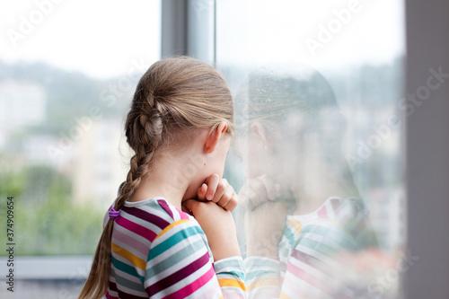 Fotografie, Obraz Sad child looking through rainy window at home