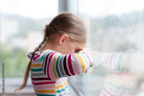 Fotografie, Obraz Sad child looking through window durin rain