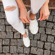 canvas print picture - Woman in trendy denim white clothes tying laces on fashion sneakers. View from above.