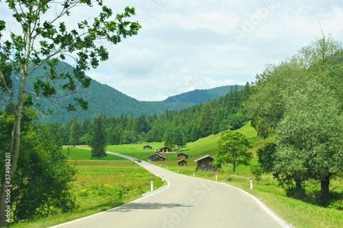Foto Landstrasse in Österreich zwischen Wald, Wiesen und Bergen