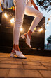 canvas print picture - Women's fashion female leg in jeans and shoes near the light bulbs in the night city. Close-up.