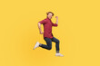 Enthusiastic happy lively guy in casual outfit jumping high trampoline, running fast quickly in air, hurry for sale. Life people energy concept. full length studio shot isolated on yellow background