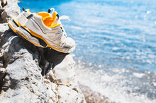 A Pair Of Men White Sneakers Stands On A Stone By The Sea - Time For Swimming - Resort Tourism And Recreation