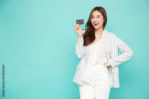 Photo Young beautiful Asian woman smiling, showing, presenting credit card for making